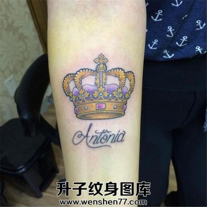 女孩小臂内侧的皇冠加英文纹身