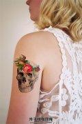 女生大臂清新的骷髅燕子花朵纹身