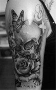 女性大臂黑灰骷髅玫瑰蝴蝶纹身