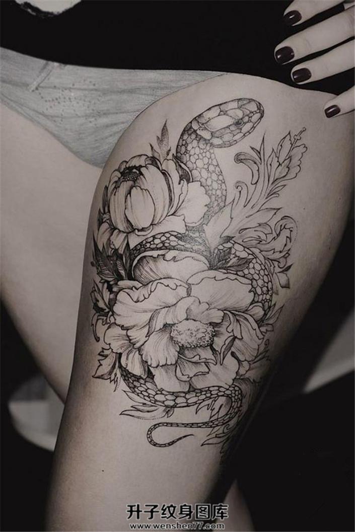 女性大腿上的蛇与牡丹纹身