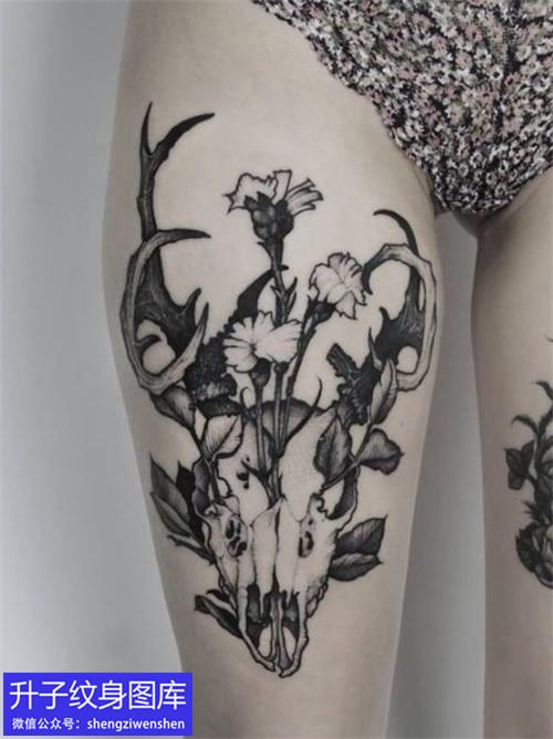 大腿的骷髅骨架与植物花纹身图案